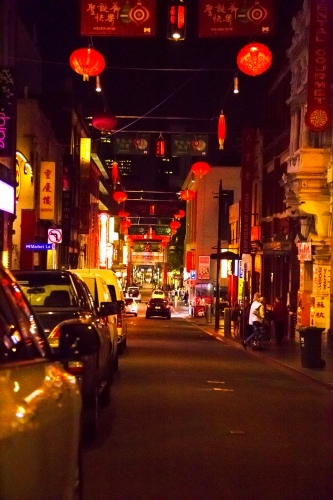 Cars parked on street in Chinatown at night