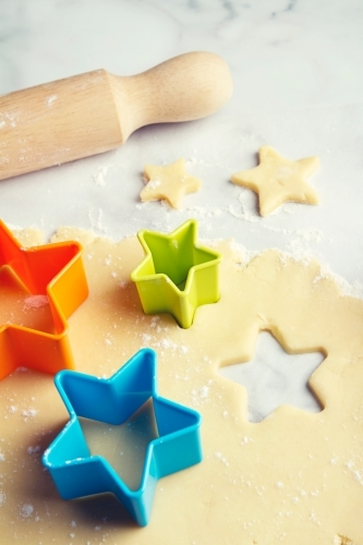 Colored star shaped cookie cutters in dough vertical