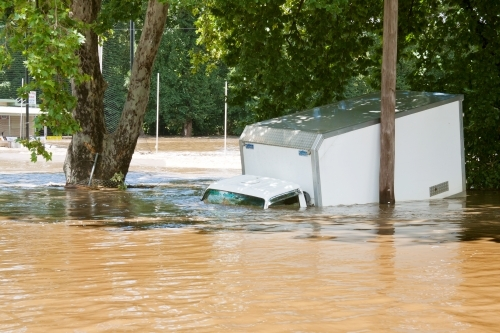 A delivery truck half submerged in flood waters