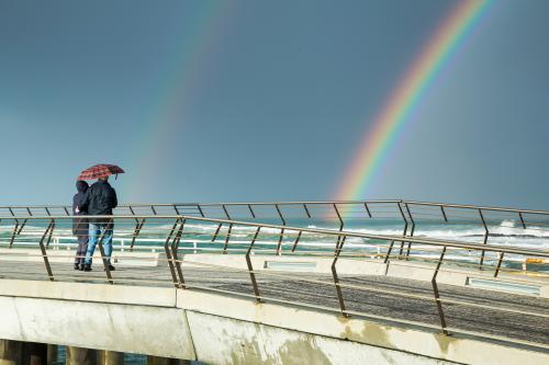 A couple walk on a jetty with an umbrella looking at a rainbow
