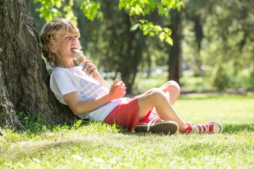 A young boy sitting against a tree licking an ice cream