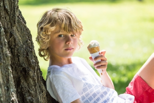 A young boy sitting against a tree holding an ice cream
