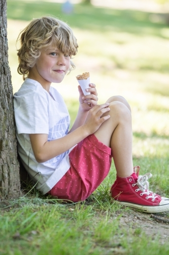 A young boy sitting against a tree eating an ice cream and smiling