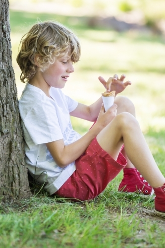 A young boy poking his finger into an ice cream cone