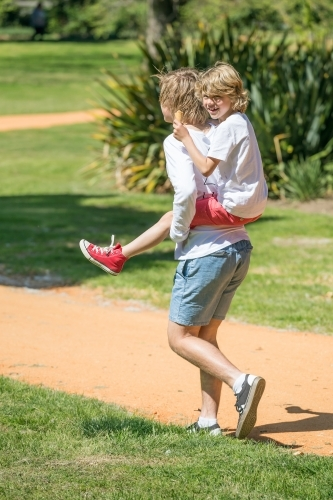 A teenage boy piggy backs his little brother