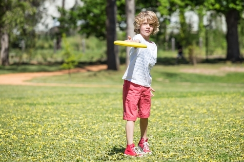 A young boy throwing a frisbee in the park
