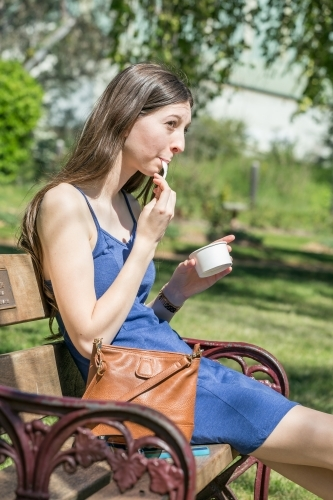 A young lady sits on a park bench eating icecream out of a cup
