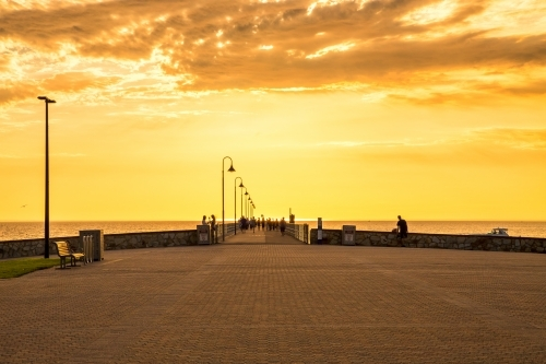 People walking on a jetty with a golden sunset