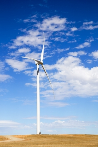 Single wind turbine against blue sky with white clouds
