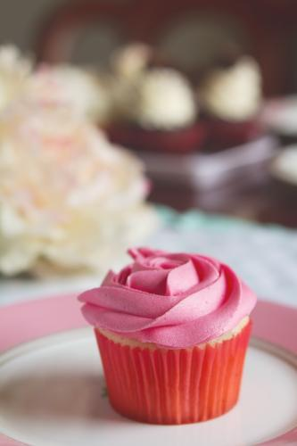 Pink vanilla rose cupcake with blurred cakes behind