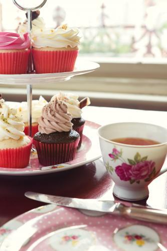 High tea with cupcake stand and cup of tea in vintage crockery