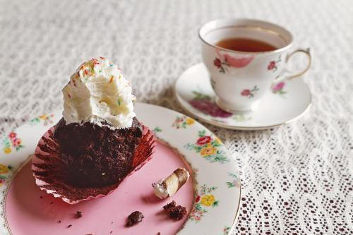 Half eaten chocolate cupcake with cup of tea in vintage crockery on lace tablecloth
