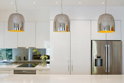 Three chrome pendant lights hanging over kitchen island bench