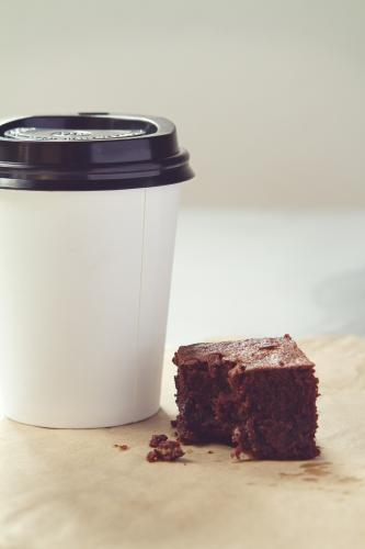 Take away coffee cup and crumbly chocolate brownie in muted tones