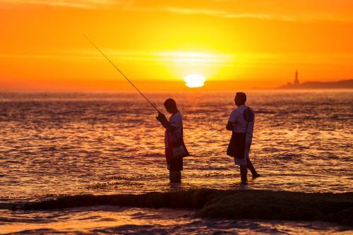 Two men fish off rocks at sunset