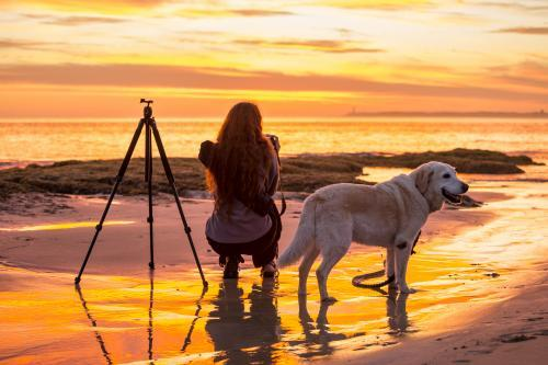 Photographer with her dog at the beach at sunset