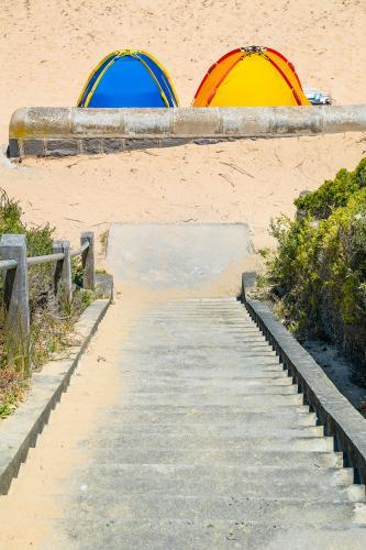 Two beach tents at the bottom of steps leading to the beach
