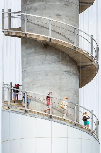 People climbing down the spiral staircase of a lookout tower.