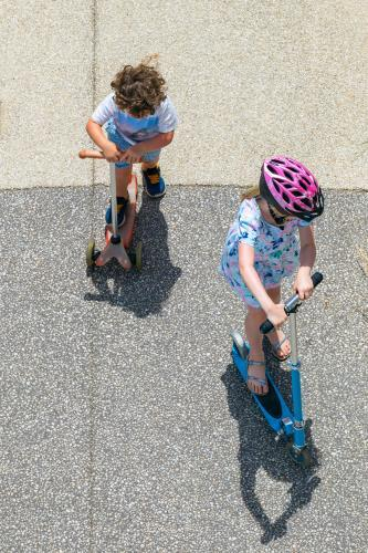 Children scootering on the pavement.