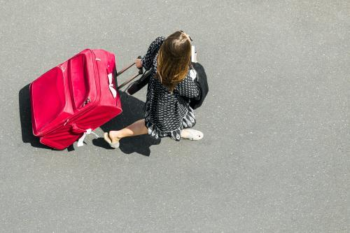 Woman pulling red suitcase behind her
