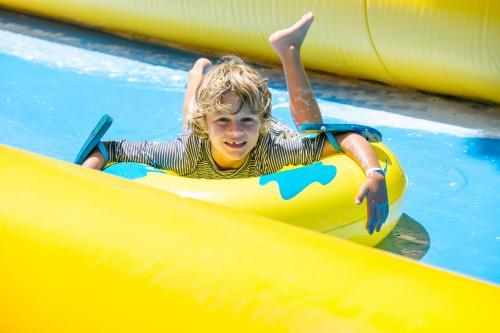 A young boy rides a waterslide