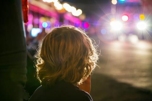 Boy watching a parade at night