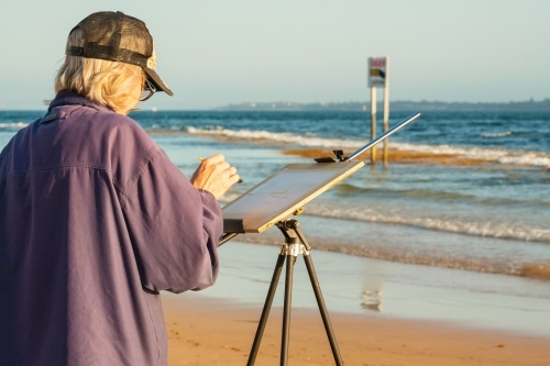 An artist painting on an easel on a beach