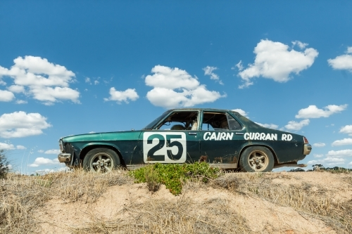 An old car sitting up on a mound of dirt against a blue sky