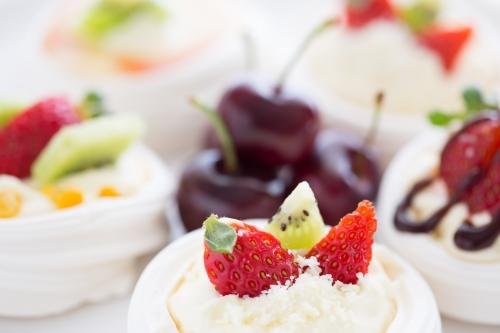 Mini Pavlova desserts topped with fruit on a white plate