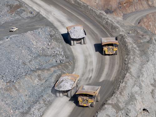 Mining trucks moving along roadway of an open cut mine