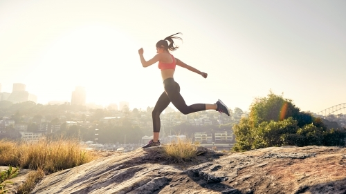 Girl running and jumping through a trail with a cityscape