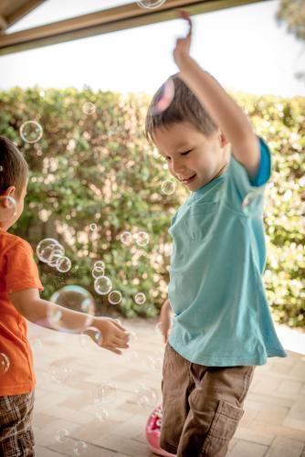 Mixed race boys play with bubbles in their suburban backyard