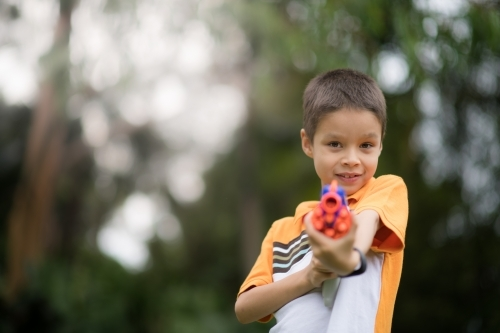 Mixed race boys playing outside with Nerf dart guns