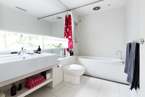 Modern renovated white mosaic tiled family bathroom with red and pink accent colors