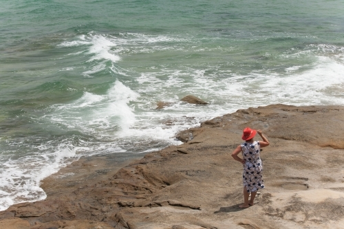 Woman standing on a rock looking out to the ocean