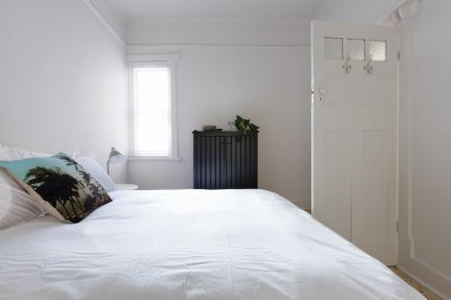 Monochrome bedroom with decorator cushion in white vintage interior