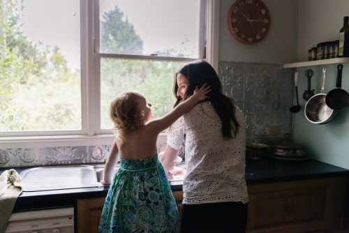 Mother and daughter at the kitchen sink