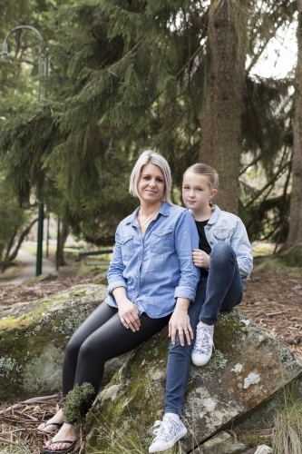 Mother and daughter sitting on a rock