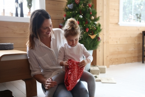 Mother and daughter unwrapping present with Christmas tree in background