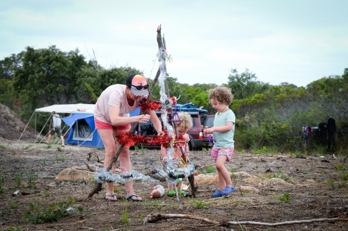 Mother and two children decorating camp Christmas tree on rural property with camper van