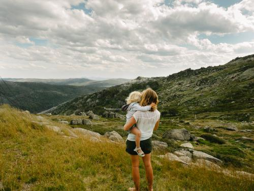 Mother cuddling daughter looking at Snowy Mountains summer landscape