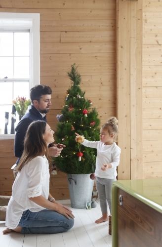 Mother, father and daughter in front of Christmas tree