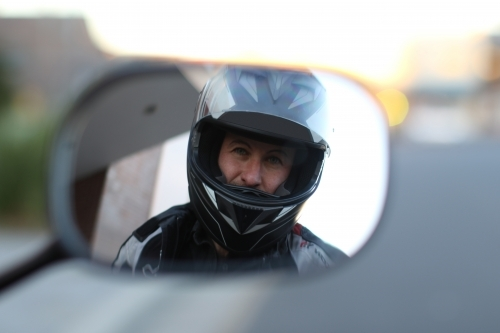 motorbike rider looking in rear view mirror