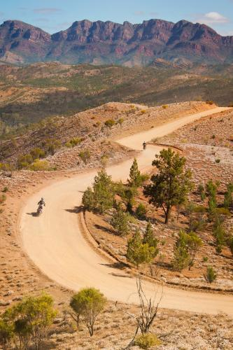 Motorbikes riding on a winding dirt road that follows a mountain spur