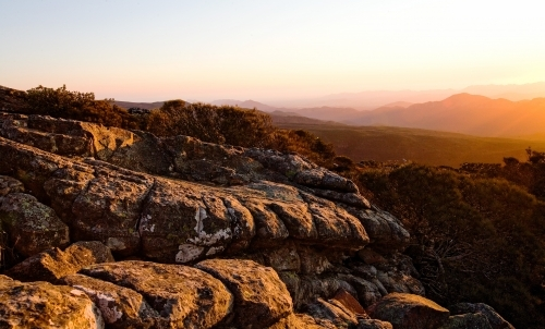 Landscape of rocks and mountain range at sunset