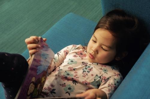 Multicultural child girl reading a book in library