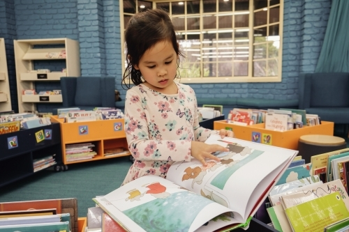 Multicultural child reading a book in library