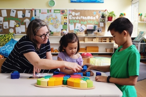 Multicultural teacher and children playing wooden blocks puzzles in kindergarten