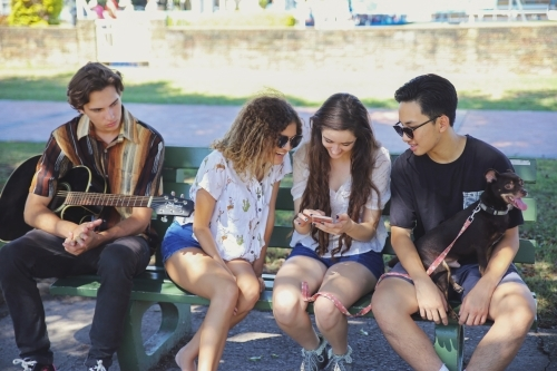 Multicultural teenagers hanging out and using mobile phone