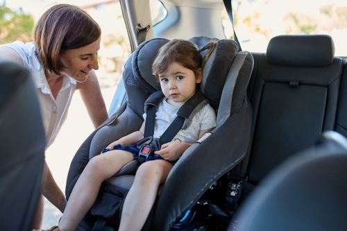 Mum putting little girl in child car seat